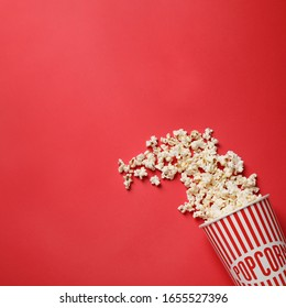 Delicious popcorn on red background, top view. Space for text