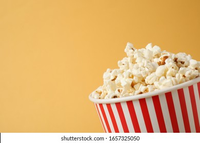 Delicious popcorn on yellow background, closeup. Space for text