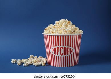 Delicious popcorn in paper bucket on blue background