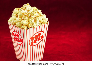 Delicious popcorn in a red striped paper cup on a red background.Selective focus.