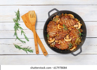 delicious Pork fillet stew with onion. mushrooms, rosemary, semi dry white wine and spices in iron stew pan on white table with wooden spatulas, easy recipe, view from above