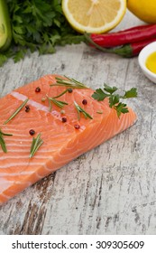 Delicious portion of fresh salmon fillet with aromatic herbs and spices over wooden vintage background