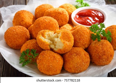 delicious potato croquettes - mashed potatoes balls breaded and deep fried, served with ketchup on white plate, view from above, close-up