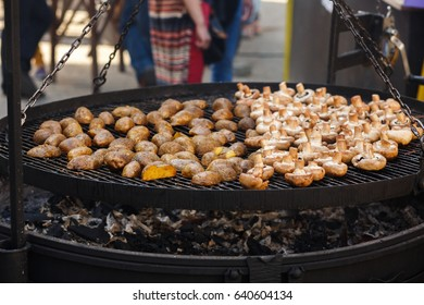 delicious potato and mushrooms roasting on open grill, outdoor kitchen. food festival in city. tasty grilled vegetables, food-court. summer picnic.
