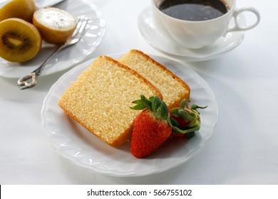 Delicious pound cake, kiwi, strawberry and espresso coffee put on white wood background.