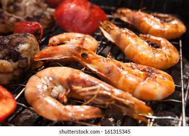 delicious prawn spit on grill with flames in background