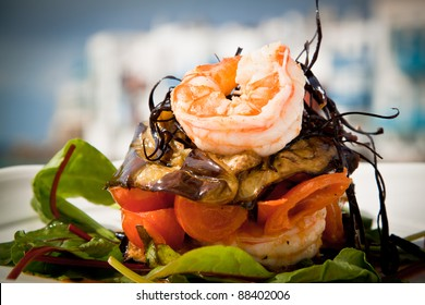 Delicious prawn starter with salad, aubergine and tomato.
