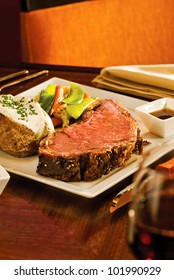A delicious Prime Rib dinner with potato and extras. Narrow focus on the meat