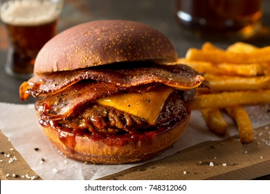 A delicious pub style bacon cheeseburger with barbecue sauce and french fries.