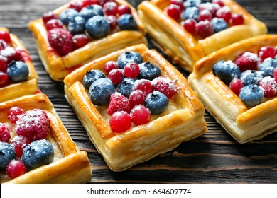 Delicious puff pastries with berries and sugar powder on wooden background