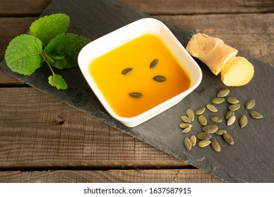 delicious pumpkin soup in a soup bowl with ginger, pumpkin seeds and mint