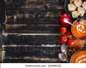Delicious pumpkin soup with heavy cream on dark rustic wooden table with red bell pepper, toasts. Autumn/Halloween/Thanksgiving day background. Top view. Space for text
