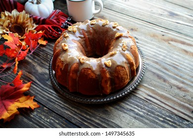 Delicious, Pumpkin Spice Bundt Cake frosted with brown sugar frosting and walnuts with Autumn leaves and coffee over a rustic wooden table background. Image shot from above. Fall foods.