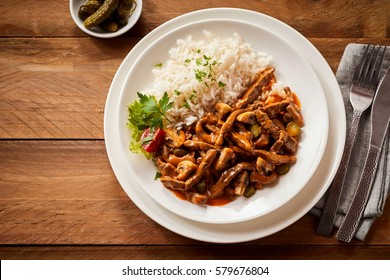 Delicious ragout with pickled cucumber seasoned with spicy chili peppers and served in a white dish on a rustic wood table viewed from above