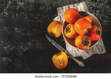 Delicious raw ripe persimmon fruit on dark rusty metal background copy space top view
