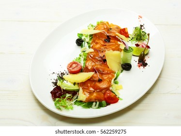 Delicious red fish or salmon fillet slices, sashimi, garnished with cheese and colorful vegetables on plate on white background. Modern molecular gastronomy