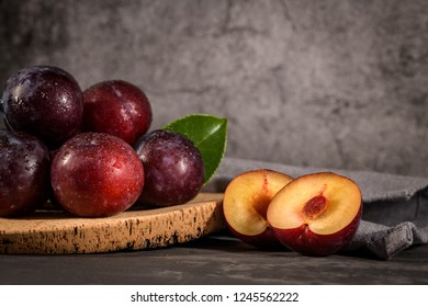 Delicious red plums in a cork plate on kitchen countertop.