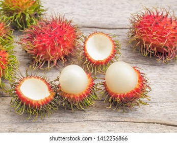 Delicious Red Ripe Rambutan fruits (Nephelium lappaceum) on wood texture background.