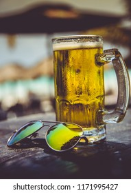 delicious refreshing cold mug of beer and sunglasses in a sunny day at the caribe,
