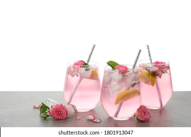 Delicious refreshing drink with rose flowers and lemon slices on light grey table against white background