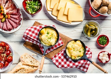 Delicious restaurant dinner with Swiss raclette cheese sliced and melted on potato served with cold meats, bread, pickles and herbs on rustic red and white napkins over a white wood table, top view