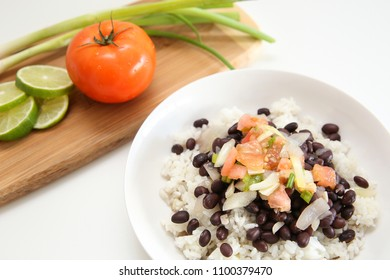 Delicious rice and black bean followed by a wooden board with delicious tomato, lime, and chive