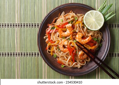 Delicious rice noodles with shrimp close-up on a plate. horizontal view from above