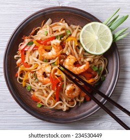 Delicious rice noodles with shrimp and vegetables close-up on a plate. top view