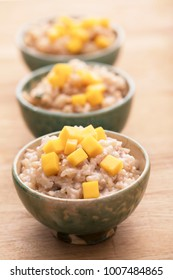 Delicious rice pudding in bowls topped with fresh mango.