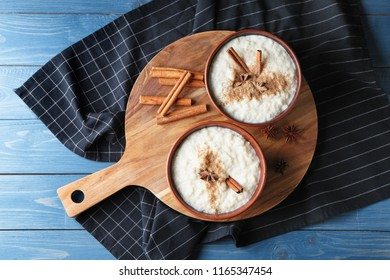 Delicious rice pudding with cinnamon and anise in bowls on wooden board