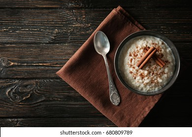 Delicious rice pudding with cinnamon in bowl on wooden background