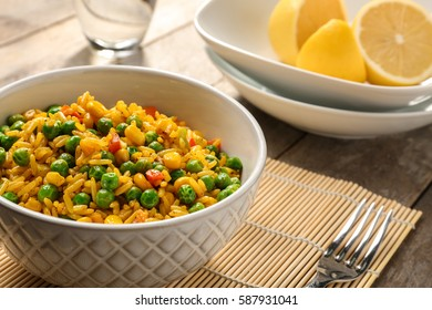Delicious rice with vegetables in a bowl on table
