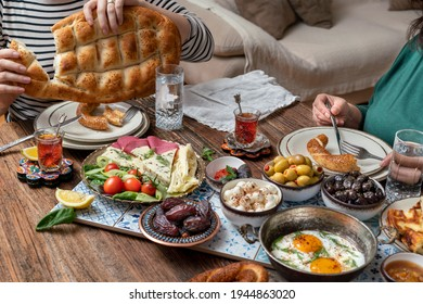 Delicious rich Traditional Turkish breakfast include tomatoes, cucumbers, cheese, butter, eggs, honey, bread, bagels, olives and tea cups. Ramadan Suhoor aka Sahur (morning meal before fasting).