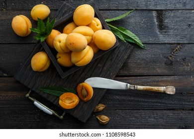 Delicious ripe apricots in a wooden box on dark wooden background, rustic style