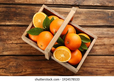 Delicious ripe oranges in basket on wooden table, top view