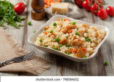 Delicious risotto with chicken and green peas. Front view.