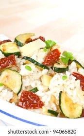 Delicious risotto close up with dry tomatoes, zucchini pieces and fresh herbs on white plate. Culinary vegetarian cooking.