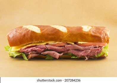 A delicious roast beef sandwich on a pretzel bun