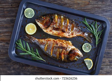 delicious roast dorado or sea bream fish with lemon and orange slices, spices, and rosemary on baking sheets on wooden table, view from above