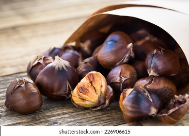 Delicious roasted chestnuts ready to eat on rustic wooden board