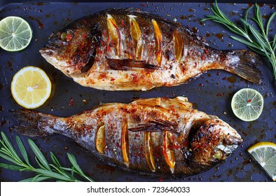 delicious roasted dorado or Gilt-head bream fish with lemon and orange slices, spices, and fresh rosemary on baking sheet, view from above, close-up