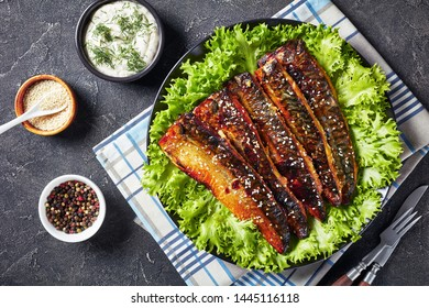 delicious roasted fillets of mackerel fish served with lettuce on a black plate on a concrete kitchen table with tartar sauce in a bowl, view from above, flat lay