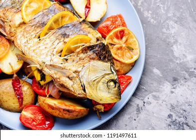 Delicious roasted fish with lemon and garnish.Tasty baked whole fish