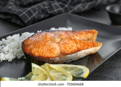 Delicious roasted salmon steak with rice on plate