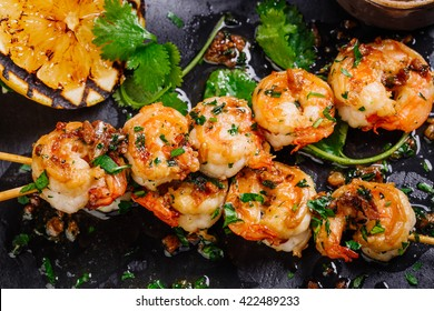 Delicious roasted shrimps on skewers with sauce and lemon