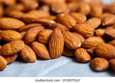 Delicious roasted sweet almonds lie in a large heap, nuts close-up.