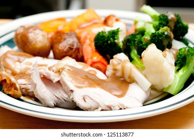 a delicious roasted turkey breast with gravy, vegetables and potatoes