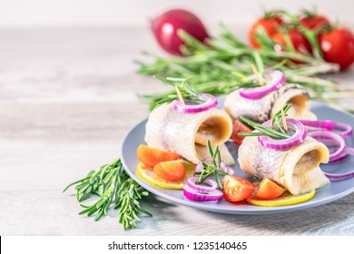 Delicious rolled herring fillet with red onion, cherry tomatoes, lemon and rosemary. Close up, restaurant serving, light gray wooden surface, copy space.