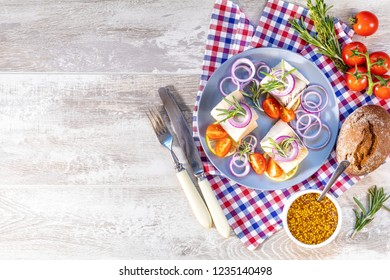 Delicious rolled herring fillet with red onion, cherry tomatoes, lemon and rosemary. Close up, restaurant serving, light gray wooden surface, copy space, top view.