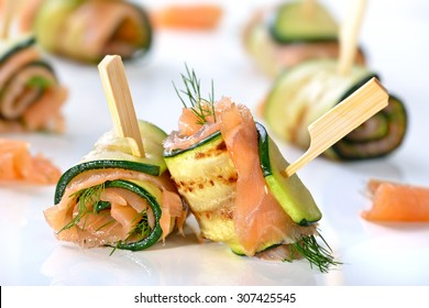 Delicious rolls of fried zucchini slices and smoked salmon with dill